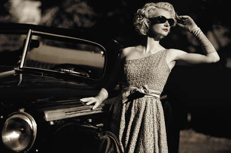 Photo pour Woman near a retro car outdoors - image libre de droit