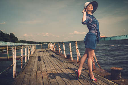 Foto für Stylish woman in white hat standing on old wooden pier  - Lizenzfreies Bild