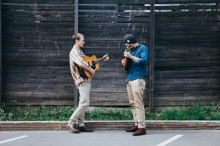 Photo for Two hipster musicians play the guitars on the street. - Royalty Free Image