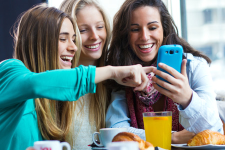 Foto de A group of friends having fun with smartphones - Imagen libre de derechos