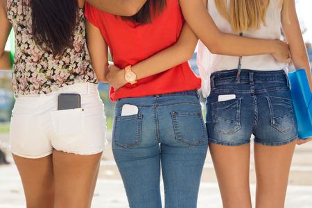 Foto de Portrait of three students girls with mobile in the pocket. - Imagen libre de derechos