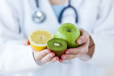 Foto de Close-up of doctor hands holding fruit such as apple, kiwi and lemon. - Imagen libre de derechos