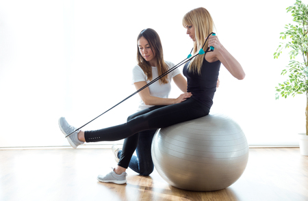 Foto de Shot of physiotherapist helping patient to do exercise on fitness ball in physio room. - Imagen libre de derechos