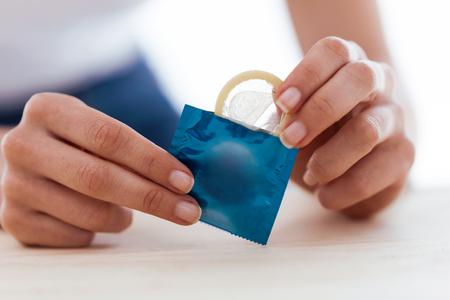 Foto de Close-up of young woman holding condom ready to use for safe sex over white background. - Imagen libre de derechos