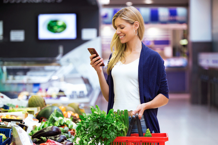 Foto de Shot of beautiful young woman looking shopping list on mobile phone while buying fresh vegetables in the market. - Imagen libre de derechos