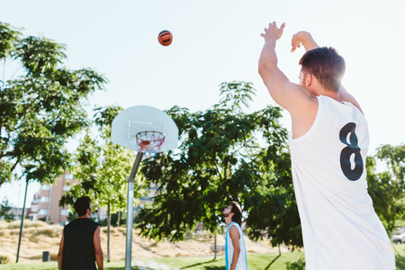 Photo pour Outdoor portrait of group of friends playing basketball on court. - image libre de droit