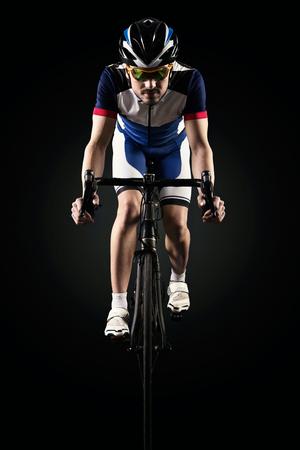 Foto de Portrait of handsome young man cycling indoor. Isolated on black. - Imagen libre de derechos