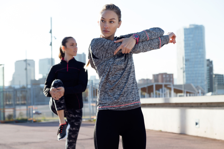 Photo pour Portrait of two fit and sporty young women doing stretching in city. - image libre de droit