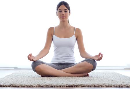 Foto de Portrait of beautiful young woman doing yoga exercises at home. - Imagen libre de derechos
