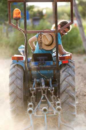 Photo pour Shot of young hipster farmer in tractor preparing land with seed cultivator in the garden. - image libre de droit