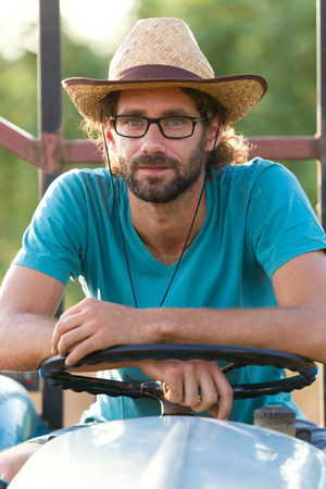 Photo pour Portrait of young hipster farmer in tractor looking at the camera in the garden. - image libre de droit