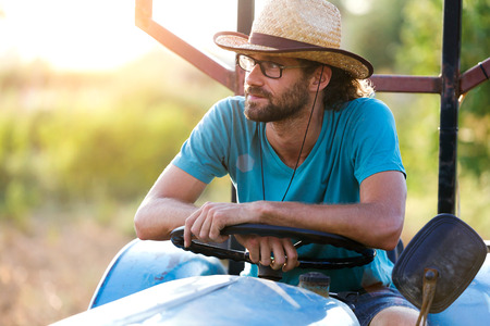 Photo pour Shot of young hipster farmer in tractor looking for his harvest in the garden. - image libre de droit