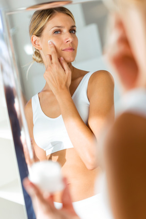 Foto de Portrait of beautiful young woman caring of her skin standing near mirror in the bathroom. - Imagen libre de derechos
