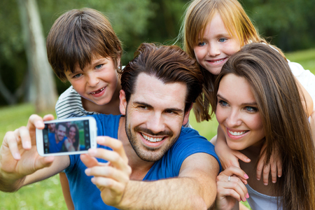 Photo for Summer scene of Happy young family taking selfies with her smartphone in the park - Royalty Free Image