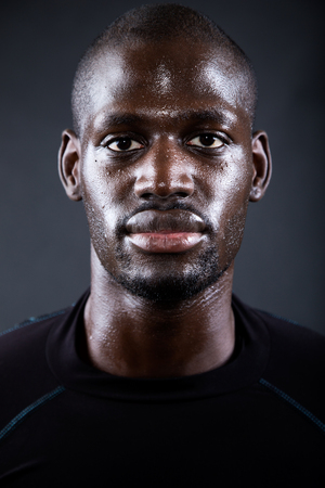 Photo for Portrait of athletic man running in black background. - Royalty Free Image