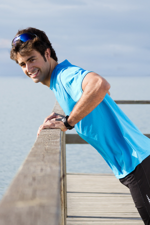 Photo for Young man doing push ups near the sea - Royalty Free Image