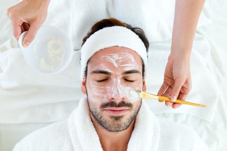 Photo pour Portrait of man with clay facial mask in beauty spa. - image libre de droit