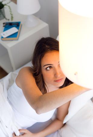 Photo pour Portrait of beautiful young woman turning off the lamp. - image libre de droit