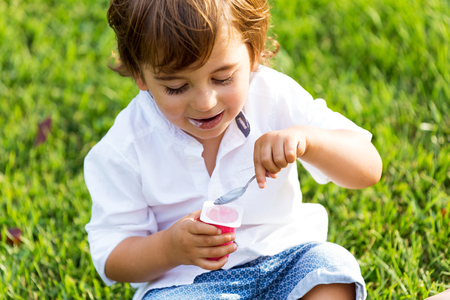 Photo for Portrait of the little boy eating yogurt in the park. - Royalty Free Image