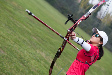 Photo for Portrait of female athlete practicing archery in stadium. - Royalty Free Image