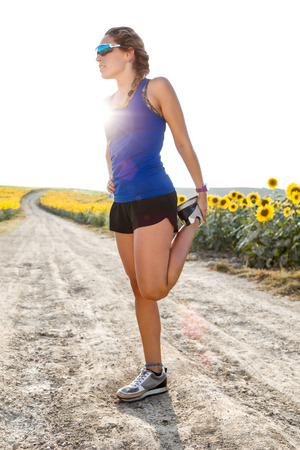 Photo pour Portrait of beautiful young woman stretching and preparing for running in countryside. - image libre de droit