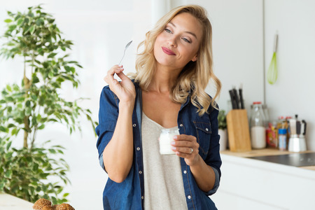 Photo for Portrait of beautiful young woman eating yogurt at home. - Royalty Free Image