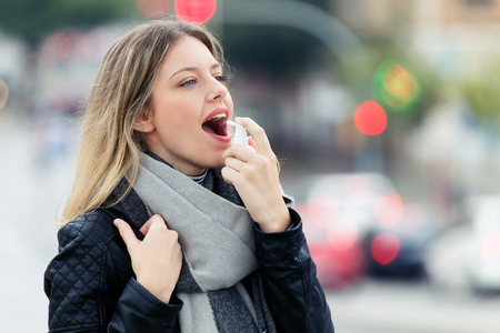 Photo pour Shot of illness young woman using a analgesic spray to soften the throat in the street. - image libre de droit