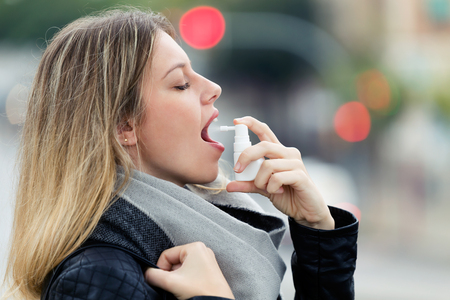 Photo for Shot of illness young woman applying a analgesic spray to soften the throat in the street. - Royalty Free Image