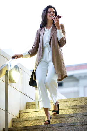 Photo for Shot of fashion young beautiful businesswoman talking with her smartphone in the street. - Royalty Free Image