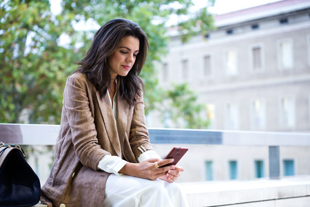 Photo for Shot of beautiful young businesswoman texting with her mobile phone in the street. - Royalty Free Image
