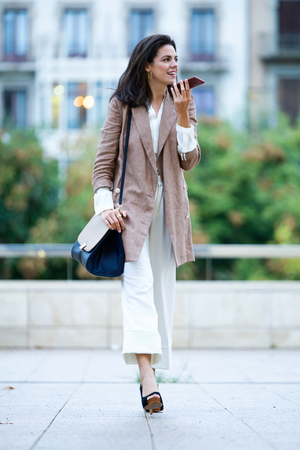 Photo for Shot of fashion young beautiful businesswoman talking with her mobile phone in the street. - Royalty Free Image