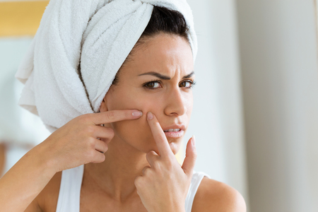 Photo pour Shot of beautiful young woman removing pimple from her face in a bathroom home. - image libre de droit