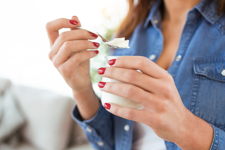 Photo for Close-up of young woman eating yogurt at home. - Royalty Free Image