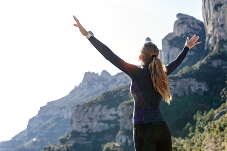 Photo pour Shot of trail runner with open arms raised while enjoying nature on mountain peak. - image libre de droit