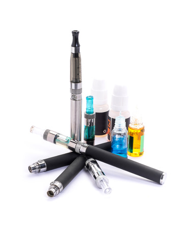 Foto de Group of electronic cigarette nicotine inhalator ,bottles with liquids behind the inhalator. isolated on white background - Imagen libre de derechos