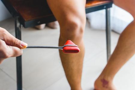 Foto de Doctor testing patellar reflex or knee-jerk reflex with red hummer jerk on young man knee. - Imagen libre de derechos
