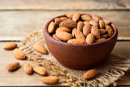 Photo for Almonds in ceramic bowl on wooden background. Selective focus. - Royalty Free Image