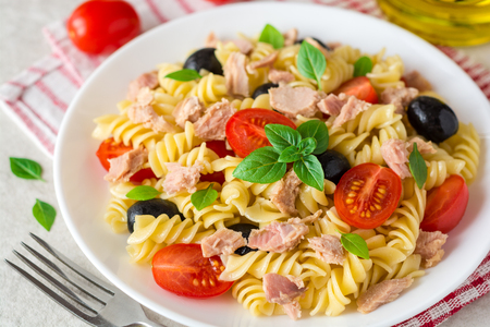 Photo pour Fusilli pasta salad with tuna, tomatoes, black olives and basil on gray stone background. Selective focus. - image libre de droit