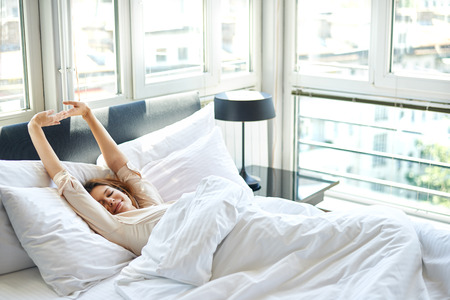 Photo pour Woman stretching in bed - image libre de droit