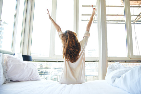 Foto de Woman stretching in bed, back view - Imagen libre de derechos