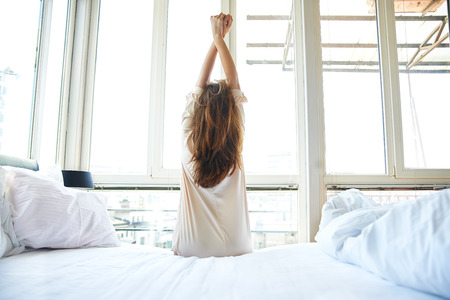 Photo pour Woman stretching in bed, back view - image libre de droit