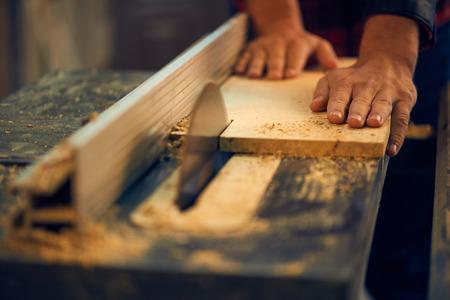 Foto de Carpenter cutting wood on circular saw - Imagen libre de derechos