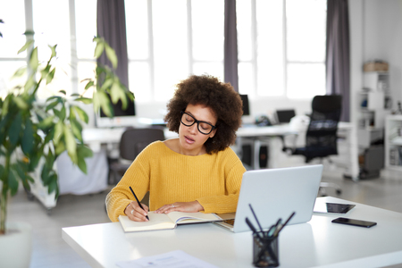 Foto de Attractive mixed race businesswoman dressed casual taking notes in notebook while sitting in modern office. On desk laptop, tablet and smart phone. - Imagen libre de derechos