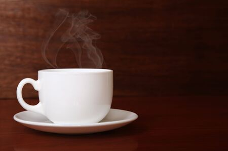 Cup of coffee over the wooden background