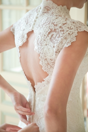 Photo pour Bride putting on her white wedding dress - image libre de droit