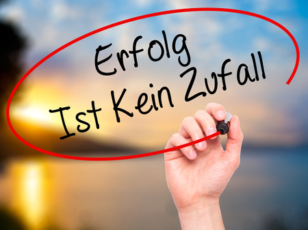 Man Hand writing Erfolg Ist Kein Zaufall (Success Is No Accident in German) with black marker on visual screen. Isolated on background. Business, technology, internet concept. Stock Photo
