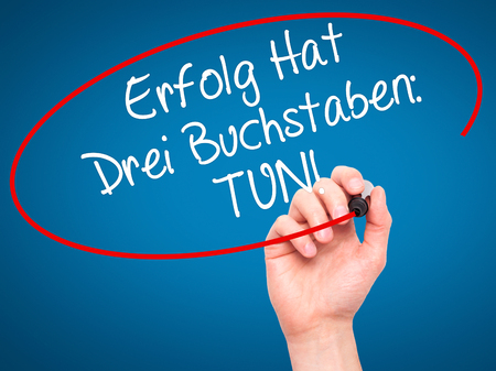 Man Hand writing Erfolg Hat Drei Buchstaben: Tun! (Success Has Three Letters: Do in German) with black marker on visual screen. Isolated on background. Business,  internet concept. Stock Photo