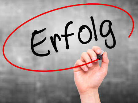 Man Hand writing Erfolg Success (in German) with black marker on visual screen. Isolated on grey. Business, technology, internet concept. Stock Photo