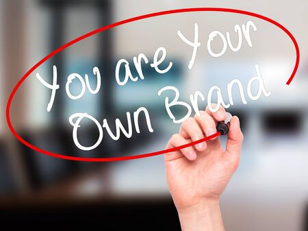 Foto de Man Hand writing You are Your Own Brand with black marker on visual screen. Isolated on office. - Imagen libre de derechos