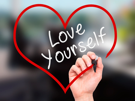 Photo pour Man Hand writing Love Yourself with marker on transparent wipe board, inside heart shape. Isolated on office. Business, internet, technology concept. Stock Photo - image libre de droit